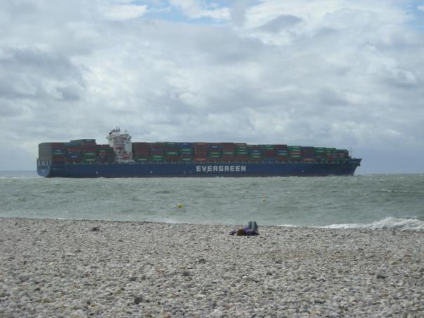 Seul au monde sur la plage du Havre, ses galets et son porte-conteneurs.